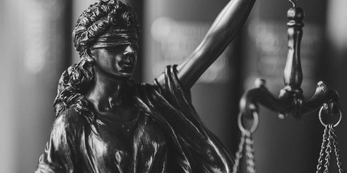 Blindfolded Justice holding up the scales with close up focus to her face over a coppery colored background