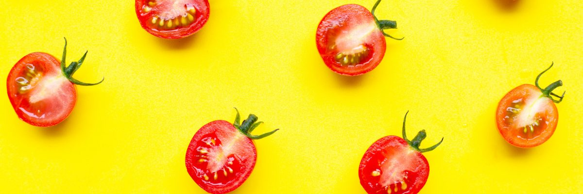 Fresh cherry tomatoes, half cut isolated on yellow background. Top view